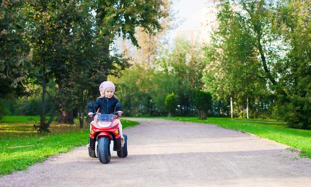 Bambine adorabili che guidano sulla motobike del bambino nel parco verde
