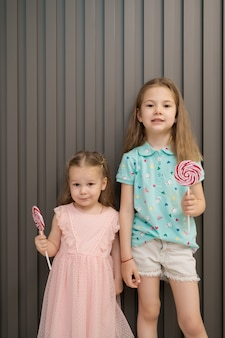 Bambine adorabili con lecca-lecca su fondo grigio