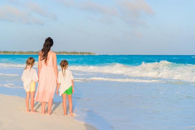 Bambine adorabili e giovane madre sulla spiaggia bianca sul tramonto