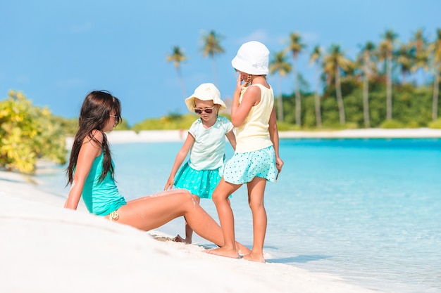 Bambine adorabili e giovane madre sulla spiaggia bianca tropicale