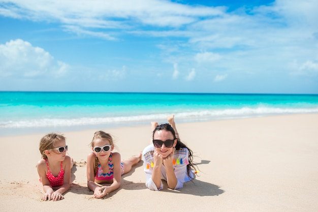 Bambine adorabili e giovane madre sulla spiaggia bianca