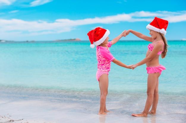 Bambine adorabili in cappelli di santa sulla spiaggia