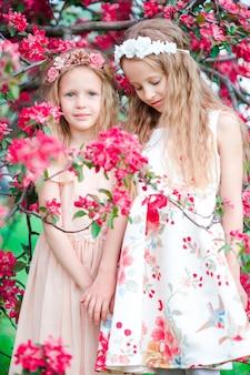 Bambine adorabili nel giardino di fioritura di melo il giorno di molla