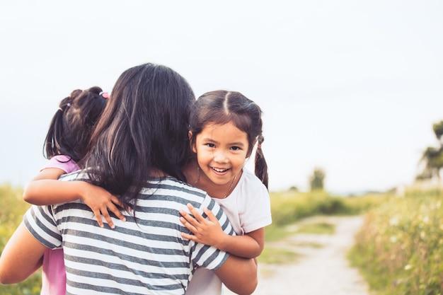 Bambine asiatiche felici che abbracciano madre e divertirsi a giocare con la madre