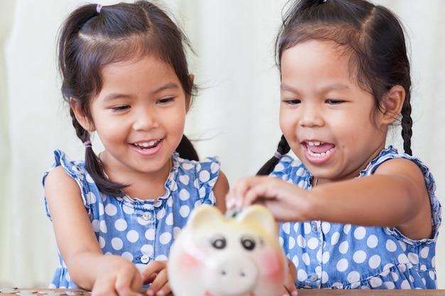 Bambine asiatiche sveglie che risparmiano soldi nel suo porcellino salvadanaio