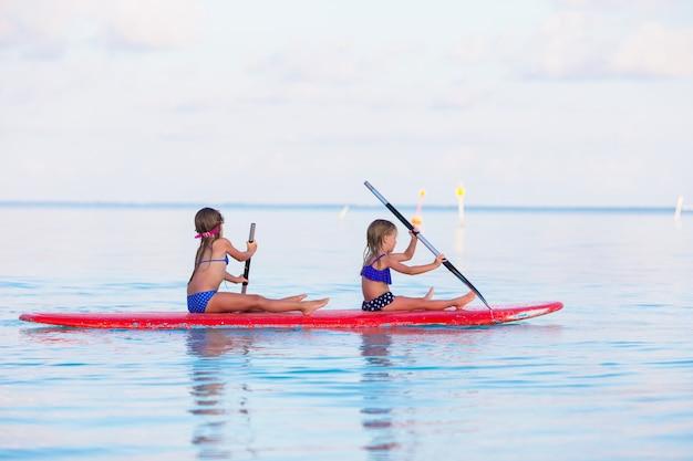 Bambine che nuotano sul surf durante le vacanze estive