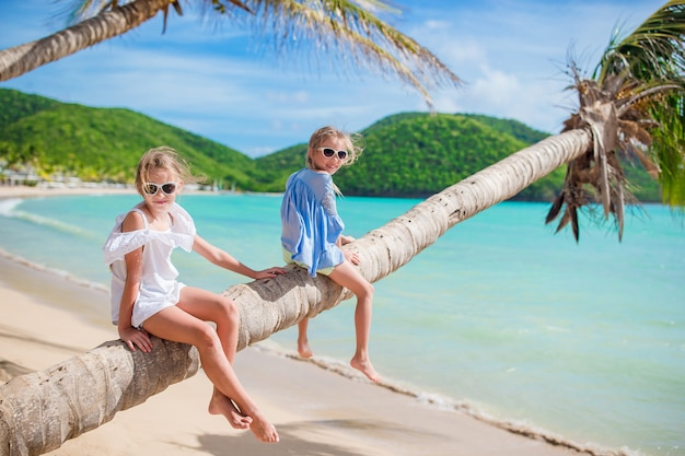 Bambine che si siedono su un tronco di palma a. la spiaggia