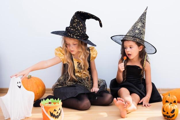Bambine di vista frontale che si siedono sul pavimento su halloween