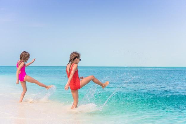 Bambine divertendosi alla spiaggia tropicale che gioca insieme alle acque basse