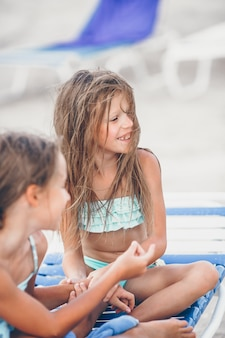 Bambine divertendosi alla spiaggia tropicale che gioca insieme