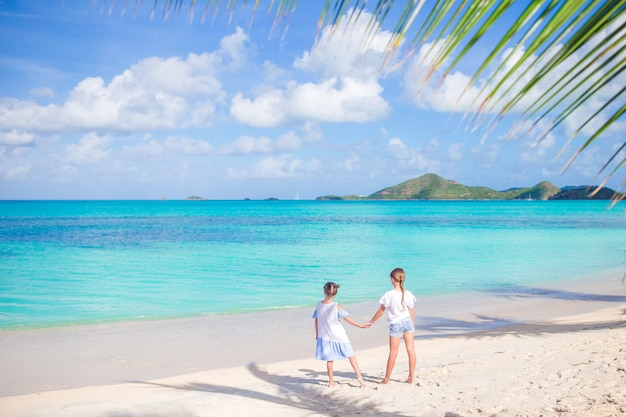 Bambine divertendosi alla spiaggia tropicale durante le vacanze estive che giocano insieme