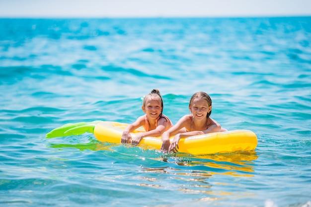 Bambine divertendosi alla spiaggia tropicale durante le vacanze estive giocando insieme