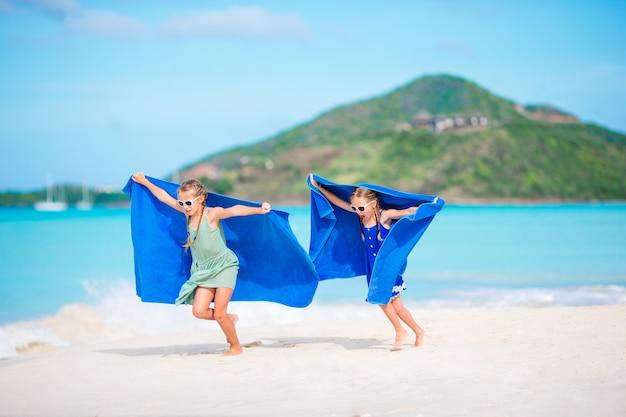 Bambine divertendosi godendo le vacanze sulla spiaggia tropicale
