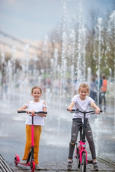 Bambine divertendosi in fontana all'aperto al giorno caldo