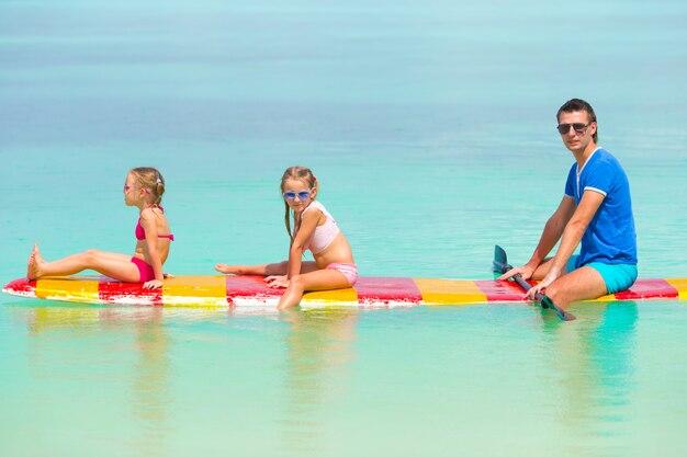 Bambine e giovani papà sulla tavola da surf durante le vacanze estive