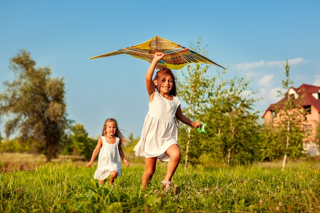 Bambine felici con l'aquilone che funziona sul prato. i bambini si divertono giocando all'aperto