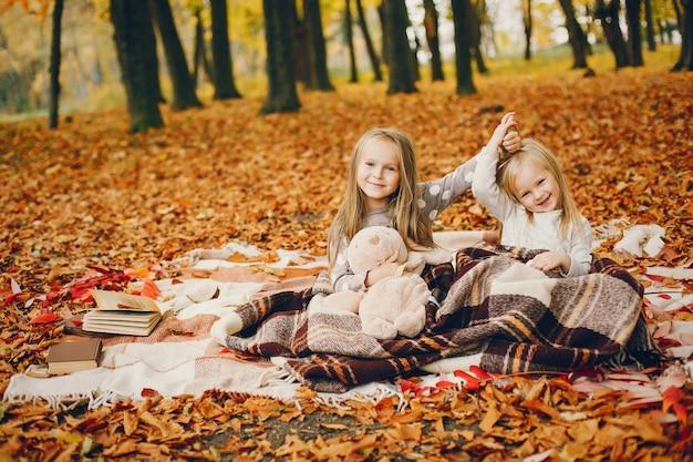 Bambine sveglie in un parco di autunno