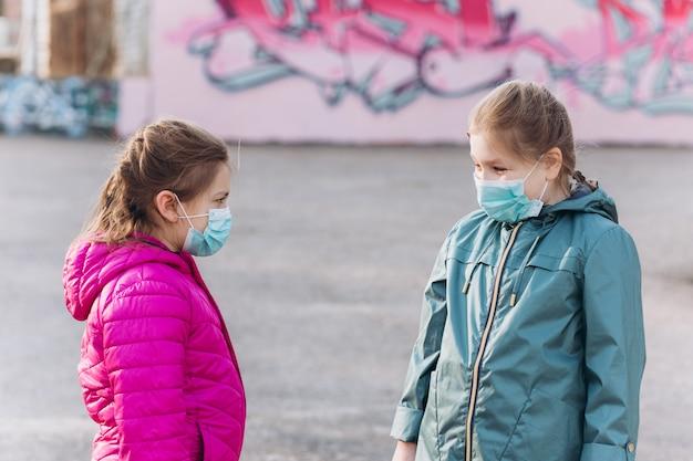 Bambine tristi e depresse in protezione sterile medica dalla maschera del virus all'aperto. assistenza sanitaria, epidemia, pandemia, concetto di malattia
