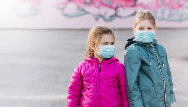 Bambine tristi in protettivo medico sterile dalla maschera del virus all'aperto. assistenza sanitaria, epidemia, pandemia, concetto di malattia