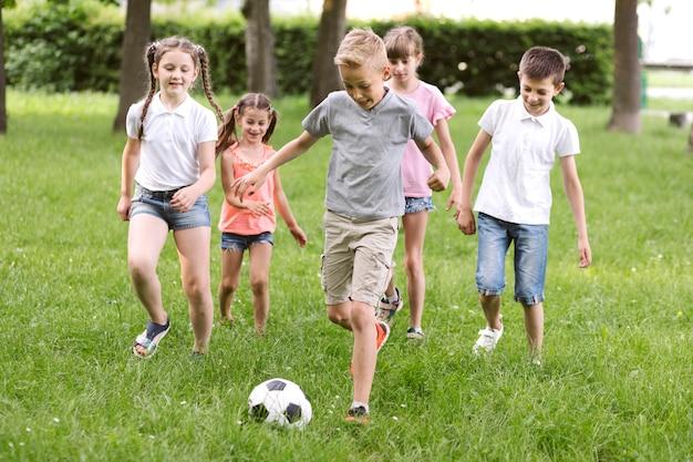 Bambini a tiro lungo che giocano a calcio
