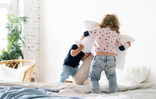Bambini a tutto campo che giocano in camera da letto