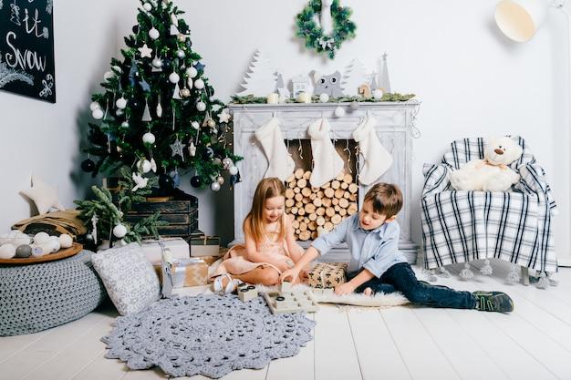 Bambini adorabili che giocano nella stanza con l'albero e il camino di cristmas. concetto di vacanze invernali.