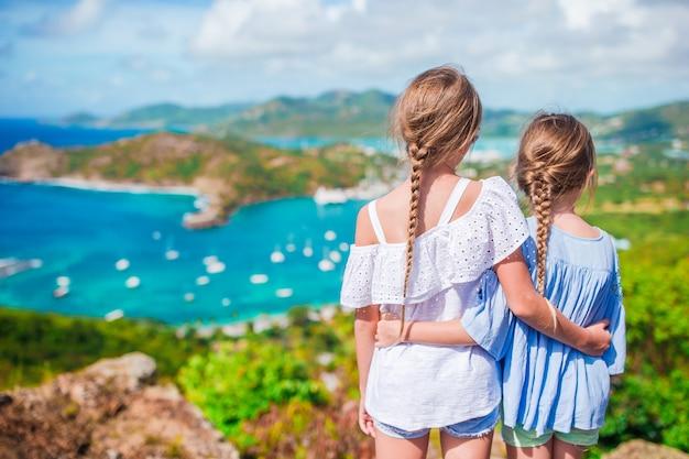 Bambini adorabili che godono della vista del porto inglese pittoresco all'antigua in mar dei caraibi