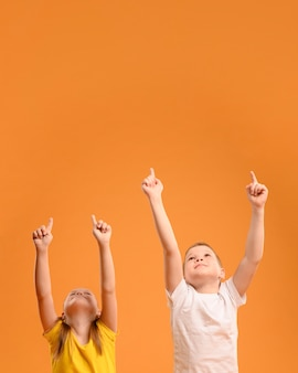 Bambini adorabili di vista frontale che indicano in su