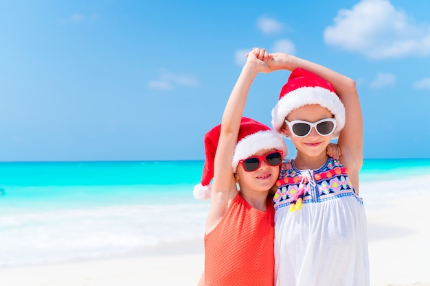 Bambini adorabili in cappello della santa durante la vacanza al mare di natale. capodanno in spiaggia