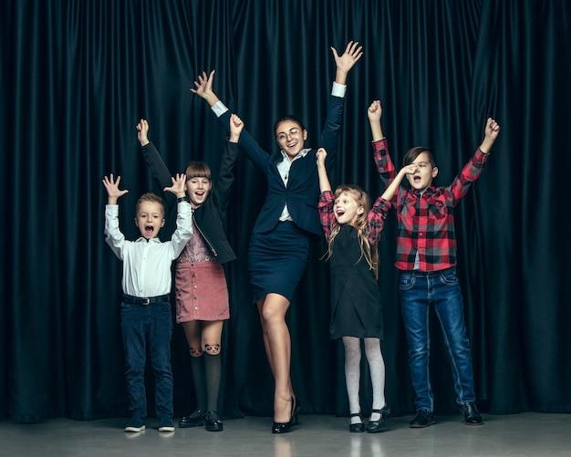 Bambini alla moda carino su sfondo scuro studio. le belle ragazze adolescenti e ragazzo che stanno insieme