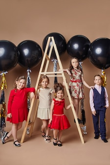 Bambini alla moda in abiti da sera e costumi che celebrano il primo giorno di scuola.