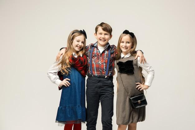 Bambini alla moda svegli sulla parete bianca