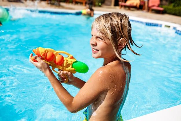 Bambini allegri che giocano a pistole ad acqua, gioendo, saltando, nuotando in piscina.