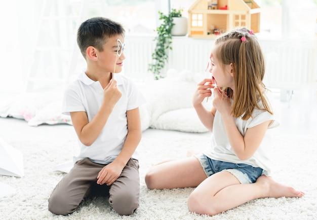 Bambini allegri con gli occhiali sui bastoni