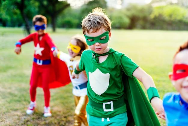 Bambini allegri dei supereroi che esprimono concetto di positività