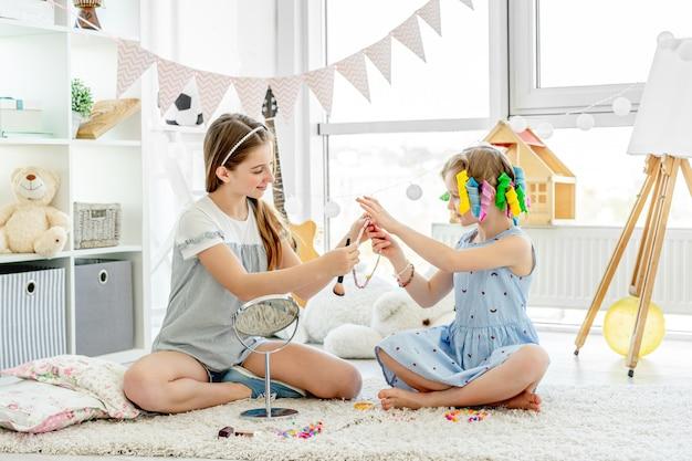 Bambini allegri delle ragazze che giocano con il trucco