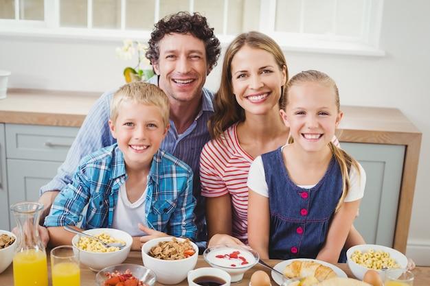 Bambini allegri e genitori facendo colazione al tavolo