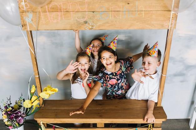 Bambini allegri vicino alla bancarella di compleanno