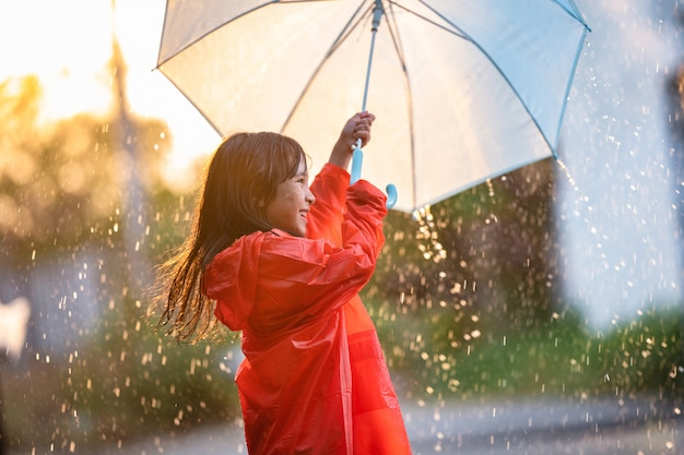 Bambini asiatici che diffondono ombrelloni che giocano sotto la pioggia, indossa indumenti impermeabili.