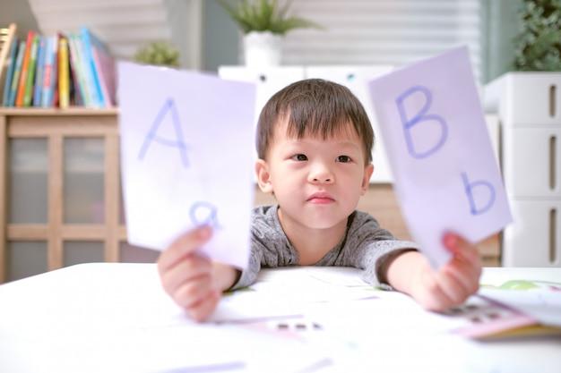Bambini asiatici che imparano l'inglese con le schede flash, insegnare ai bambini l'inglese a casa, bambino a casa, scuola materna chiusa