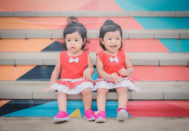 Bambini asiatici del gemello del ritratto che sorridono nel parco. tono vintage