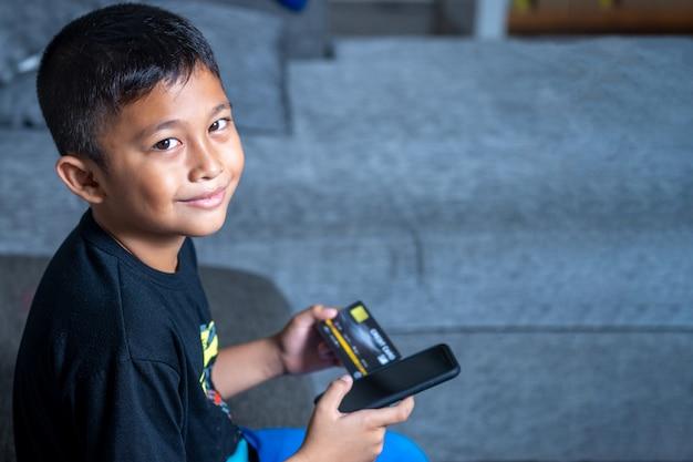Bambini asiatici di yong con pelle gialla, tenendo la carta di credito nera, computer portatile nero sulla tavola bianca.
