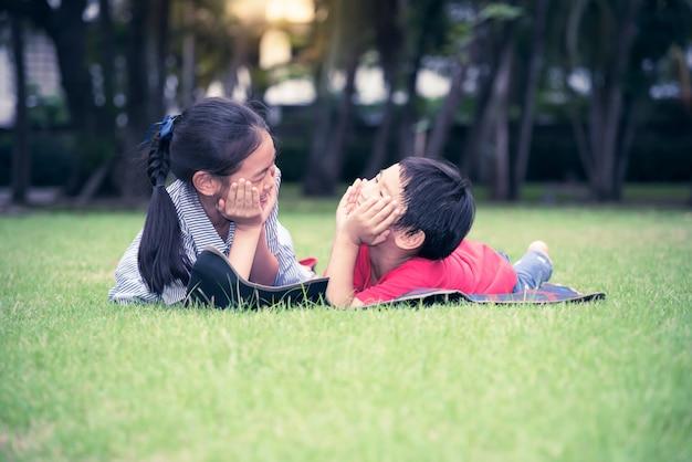 Bambini asiatici sdraiati e rilassati sul prato verde del parco sorridono divertenti e felici