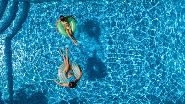 Bambini attivi in piscina vista aerea dall'alto, bambini felici nuotano su ciambelle gonfiabili e si divertono in acqua durante le vacanze in famiglia sul resort