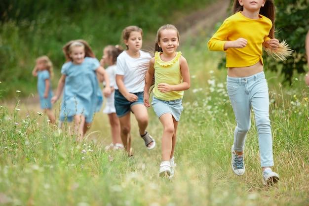 Bambini, bambini che corrono sul prato verde