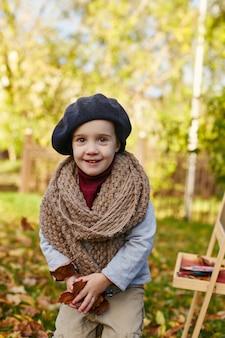 Bambini bambino in abiti primavera autunno retrò. piccolo bambino seduto sorridente in natura, sciarpa intorno al collo, tempo fresco