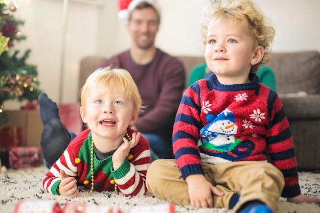 Bambini carini che guardano la tv con i genitori, indossando abiti natalizi