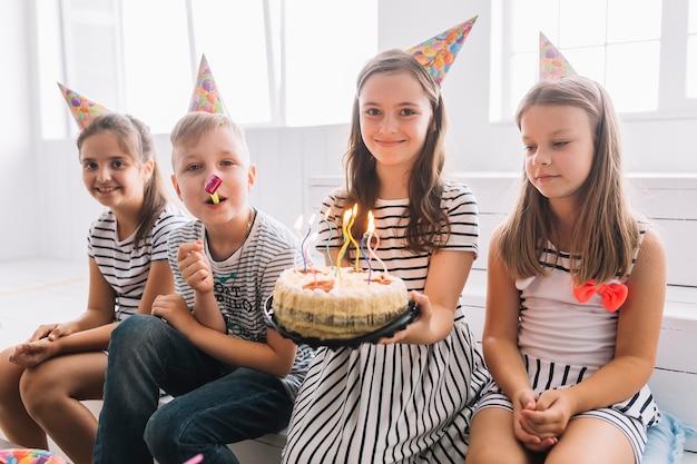 Bambini carini con torta di compleanno