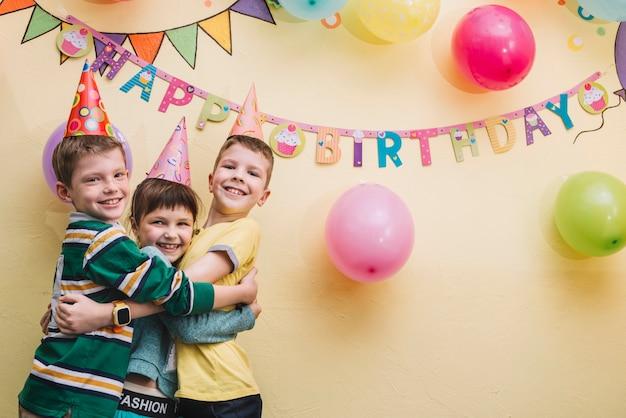 Bambini che abbracciano alla festa di compleanno