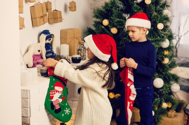 Bambini che aprono i regali di natale con il cappello di babbo natale
